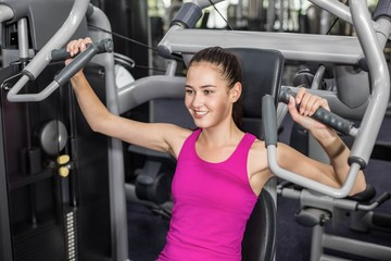 Fit woman using weight machine