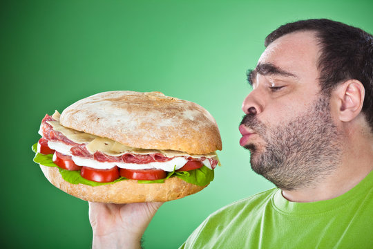 fat funny man eat a huge sandwich isolated on green