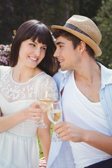 Young couple having glass of wine in garden