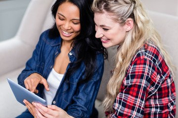 Young woman showing digital tablet to female friend