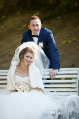 beautiful happy stylish bride with elegant groom on the bench on