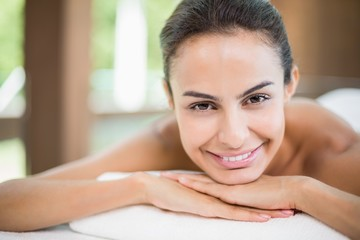 Portrait of young woman smiling while resting on massage table