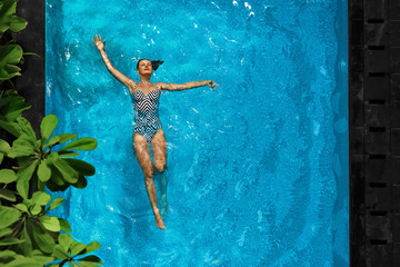 Woman In Pool Water. Beautiful Happy Girl With Sexy Fit Body Relaxing, Floating In Swimming Pool At Spa Hotel. Summer Holidays Vacation. Healthy Lifestyle. Wellness, Beauty, Health Concept. Recreation