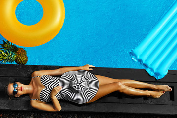 Woman Summer Fashion. Happy Sexy Smiling Girl With Fit Body, Long Legs, Healthy Skin In Bikini, Sun Hat, Sunglasses Sunbathing By Swimming Pool On Travel Holidays Vacation. Beauty, Wellness, Lifestyle