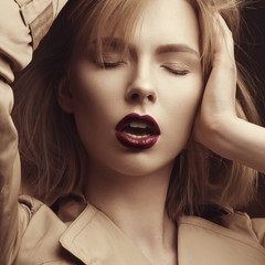 Beautiful blonde woman in a bright coat and dark lips, showing d