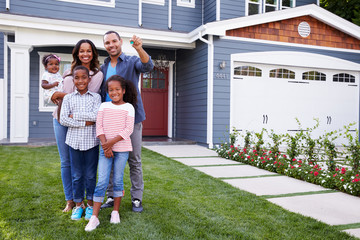 Happy black family standing outside their house, dad holding the