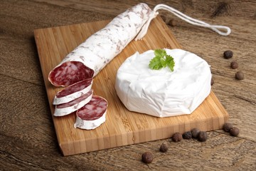 Traditional sliced salami on wooden board with brie Camembert