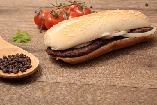 baguette with meat cutlets with onion and a spoon with pepper