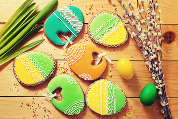 Easter homemade gingerbread cookie, willow and eggs over wooden table