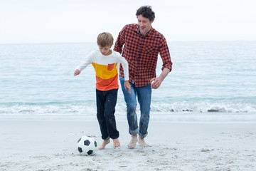 Father and son playing soccer at beach