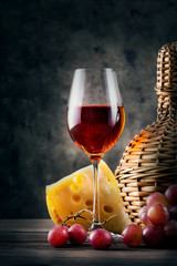 Glass of red wine with grapes and wicker bottle