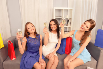 Three pretty trendy girls celebrating purchases with champagne