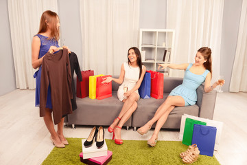 Happy woman showing her new dress to her girlfriends