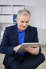 älterer geschäftsmann liest am tablet