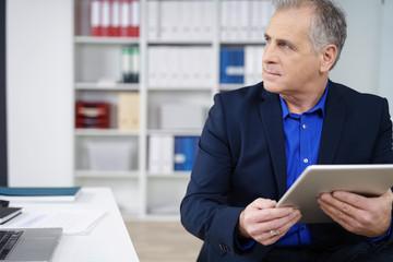 konzentrierter geschäftsmann am schreibtisch mit tablet