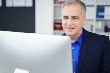 älterer geschäftsmann blickt auf seinen computer