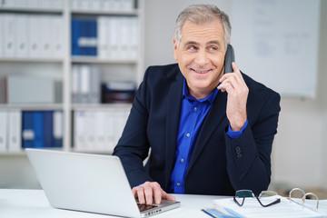 freundlicher älterer geschäftsmann am telefon