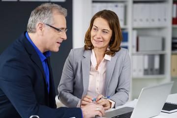 zwei manager sitzen am schreibtisch in einer besprechung