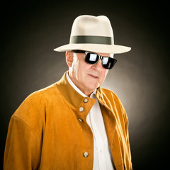 elderly fashion man portrait with hat and glasses isolated on black