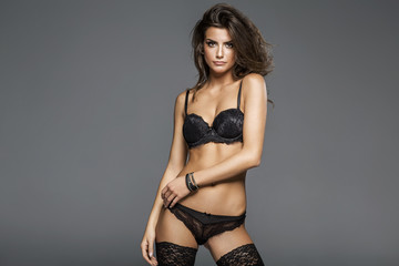 Sexy attractive brunette woman posing in fashionable lingerie in