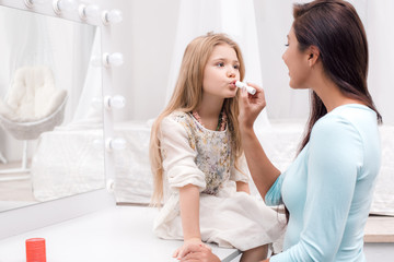 Mother and little daughter applying makeup