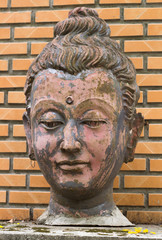 Old Buddha face statue on background