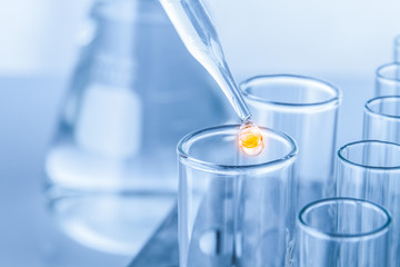 Laboratory pipette with drop of liquid over glass test tubes