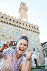 Woman tourist with photo camera showing thumbs up, Florence