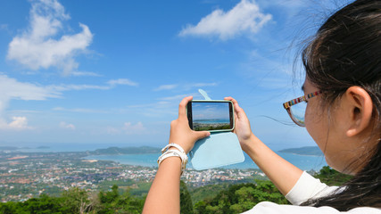 Young women tourist take photos high angle view of Ao Chalong bay and city sea side with mobile phones on top of Yot Khao Nak Kerd Hill in Phuket Province, Thailand, 16:9 wide screen