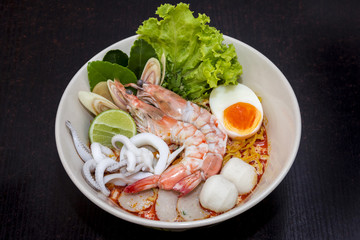close up. thai noodle seafood, eggs, fish ball in a cup on dark