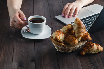 Basket with tasty fresh croissants and hot morning cup of coffee