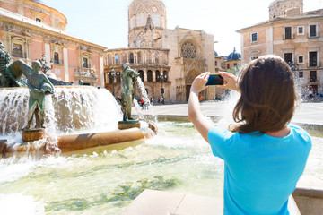 Tourist taking travel picture with phone of Cathedral in Valencia, summer holidays. Unrecognizable female young adult enjoying Spanish vacations in blue t-shirt.