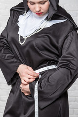 Nun measures waist volume