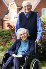 Senior Woman In Wheelchair Being Pushed By Husband