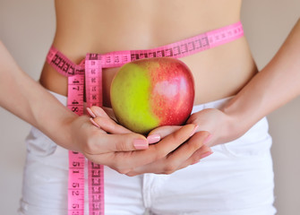 Woman measuring her waist while holding an apple