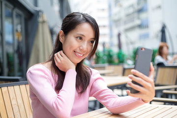 Woman take self photo in outdoor cafe