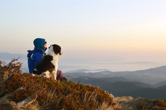 Young woman and dog admiring sunrise high in the mountain