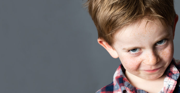 closeup portrait of a young mischievous child with freckles teasing and grumbling with fun look and joke, copy space on grey background studio