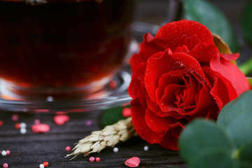 Tea in a transparent cup, color candies and a red rose