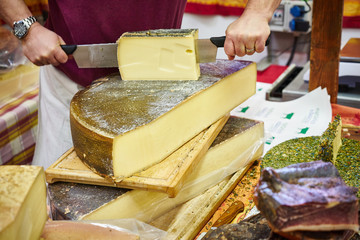 Man cutting slices of delicious cheese / Food market with abundance of high quality cheese