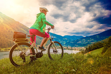 sportive woman with e-bike above a lake