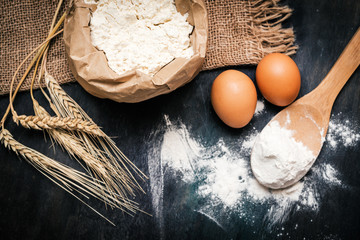 Flour and eggs on black table. Cooking process
