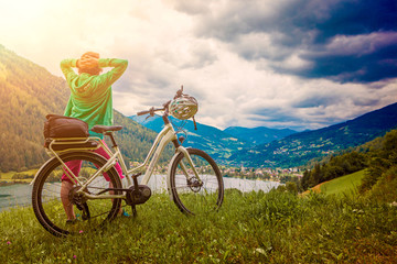 sportive woman with e-bike resting above a lake