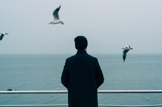 cool trendy stylish sexy handsome hipster lonely guy looking at the calm sea with seagulls back view. tourist on vacation. blank space for text or quote about life, success