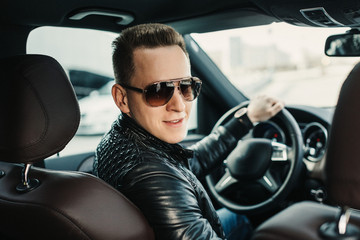 Fashionable Handsome Man in Sunglasses Sitting in his Luxury on Driver Seat. Luxury Life. Lifestyle photo. Ideal for commercial. Rental car concept