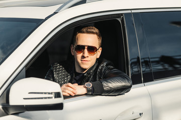 Fashionable Handsome Man in Sunglasses Sitting in his Luxury on Driver Seat. Luxury Life. Lifestyle photo. Ideal for commercial