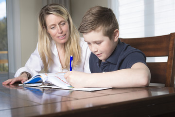mother at a table at home helping her small son with his homework