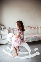 Beautiful smiling baby girl on a toy wooden horse. Brunette, toy, game