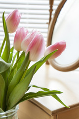 Beautiful bouquet of pink tulips and mirror on backlight background