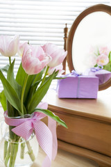 Pink tulips, gift and mirror, backlight background